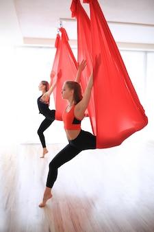Deux femmes entraînant la gymnastique dans le centre de yoga