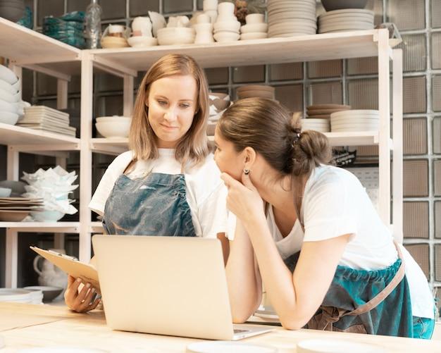 Deux femmes entrepreneur avec ordinateur portable dans l'atelier de travail artisanal