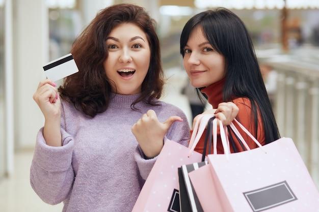 Deux femmes excitées posant dans un centre commercial et tenant des sacs avec des achats, une femme en pull lilas détient une carte de crédit et pointe le pouce de côté, les femmes font du shopping.