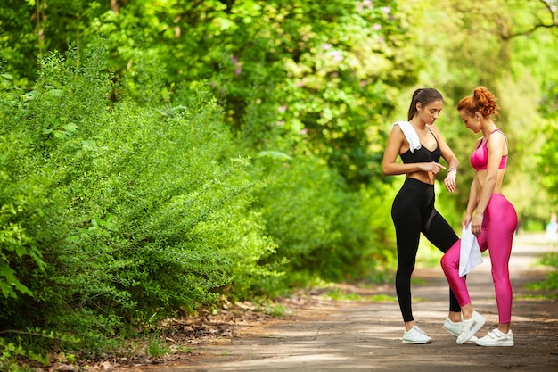 Deux femmes exerçant dans le parc. belle jeune femme faisant des exercices en plein air