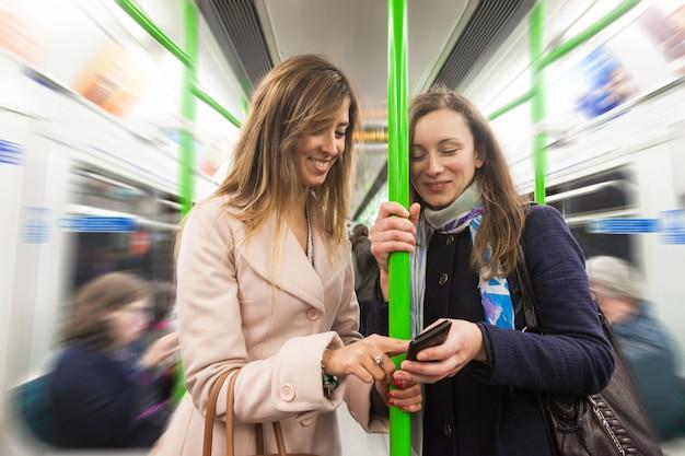 Deux femmes faisant la navette avec un tube à londres.