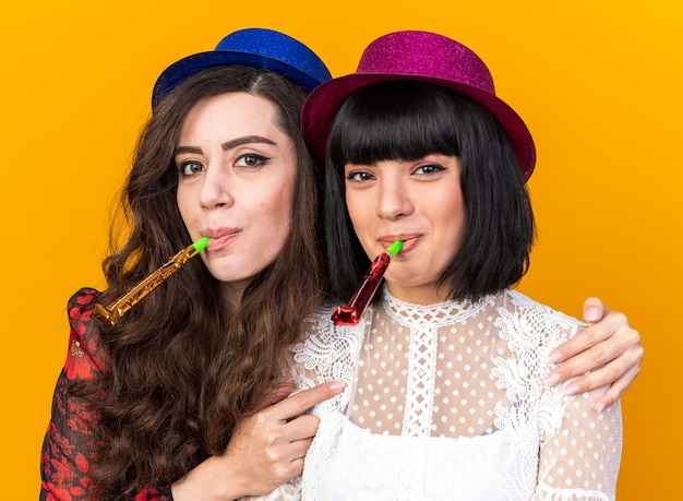 Deux femmes de fête heureuses portant un chapeau de fête toutes les deux soufflant une corne de fête regardant devant une autre fille tenant une autre fille par les épaules par derrière isolées sur un mur orange
