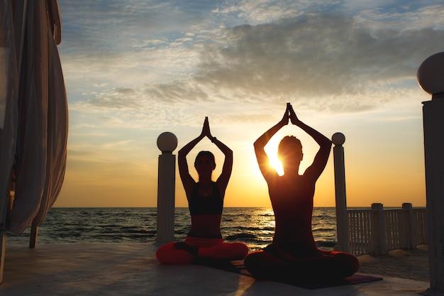 Deux femmes font du yoga au lever du soleil près de la mer