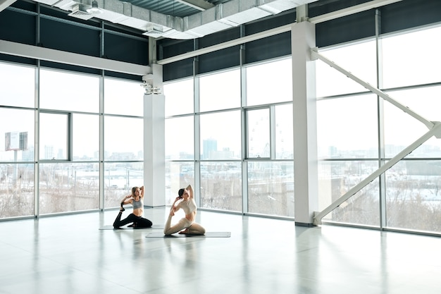 Deux femmes en forme active exerçant sur des tapis avec leurs bras derrière la tête pendant l'entraînement de remise en forme dans un grand centre de loisirs contemporain