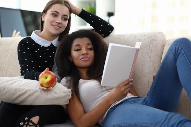 Deux femmes frend lire livre s'asseoir sur l'entraîneur contre