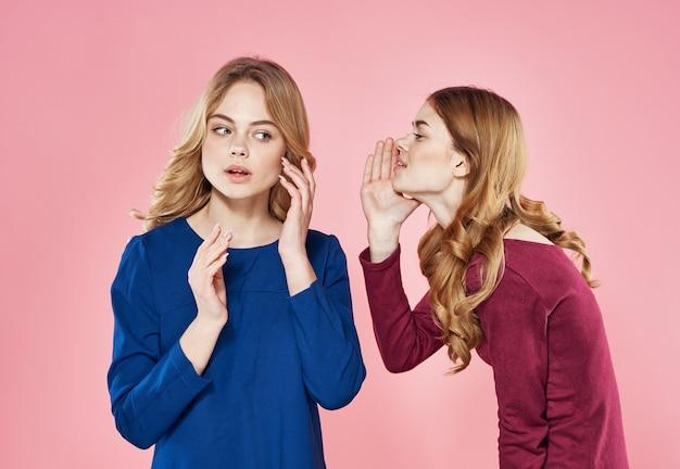 Deux femmes gaies communiquant un style élégant style de vie fond rose