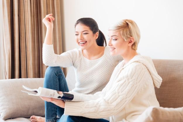 Deux femmes gaies lisant un magazine sur le canapé à la maison