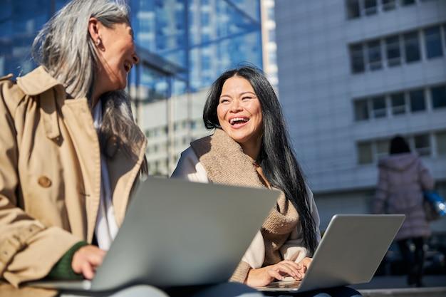 Deux femmes gaies utilisant un ordinateur portable moderne à l'extérieur