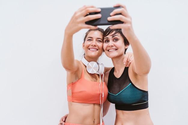 Deux femmes, gymnase, conversation, heureux, écouter musique, sur, téléphone portable