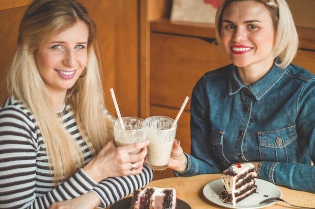 Deux femmes heureuses assises dans un café, boivent un cocktail, se racontent des histoires amusantes, étant de bonne humeur, riant joyeusement. meilleurs amis
