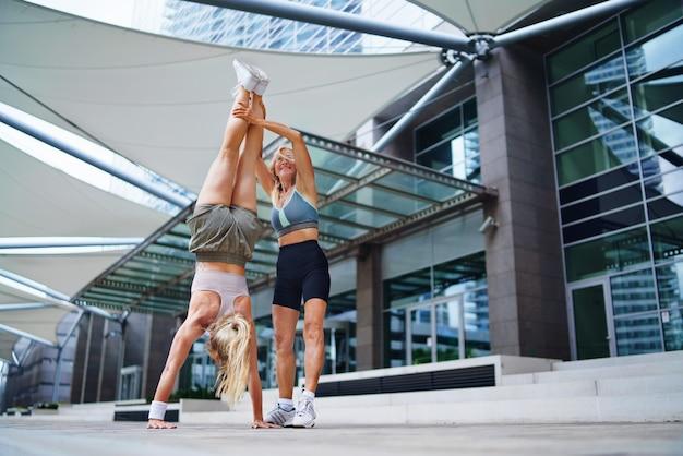 Deux femmes heureuses faisant de l'exercice à l'extérieur en ville, concept de mode de vie sain.