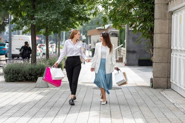 Deux femmes heureuses marchant dans la rue après avoir fait du shopping dans la zone commerciale de la ville