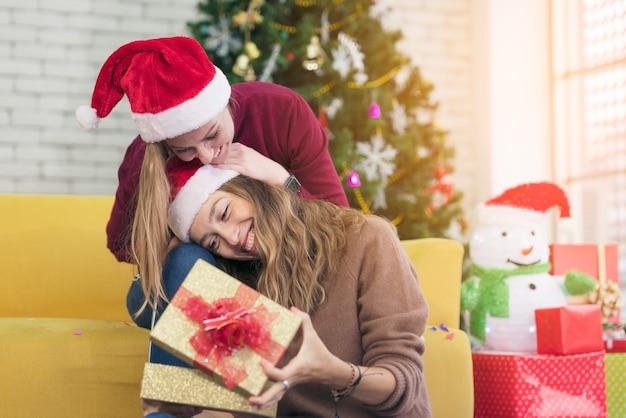 Deux femmes heureuses meilleures amies avec scaft et santa hat excité et surpris ouverture boîte cadeau présente dans le salon à la maison
