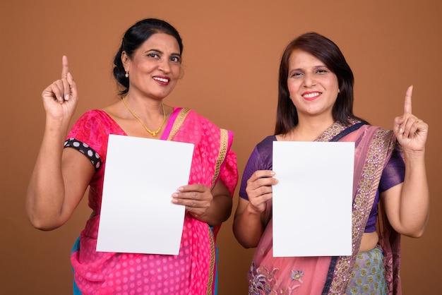Deux femmes indiennes matures portant des vêtements traditionnels indiens sari avec du papier vierge