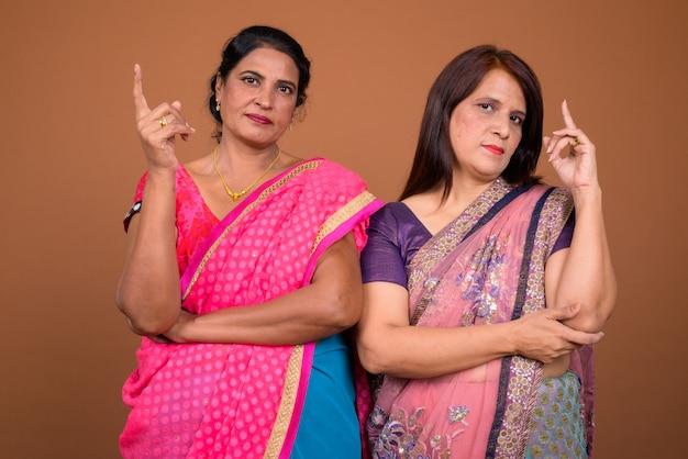 Deux femmes indiennes matures portant des vêtements traditionnels indiens sari ensemble pointant