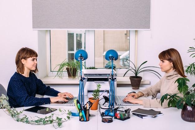 Deux femmes jumelles travaillent en face l'une de l'autre au bureau sur un ordinateur portable. interaction des sœurs et des collègues de travail. la psychologie des relations de travail.