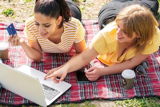 Deux femmes latina dans le parc avec ordinateur et carte de crédit en ligne sur une journée ensoleillée