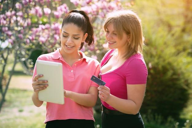 Deux femmes latina dans le parc avec tablette et carte de crédit en ligne sur une journée ensoleillée