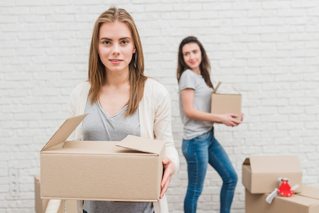 Deux femmes lesbiennes tenant des boîtes en carton à la main, debout près du mur de briques blanches