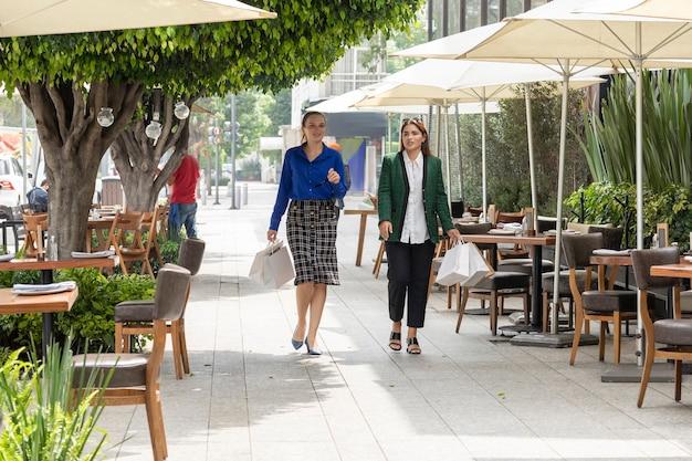 Deux femmes marchent joyeusement dans les rues de la ville après avoir fait du shopping