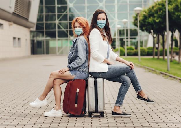 Deux femmes en masques de protection assis sur des valises en attente du vol.