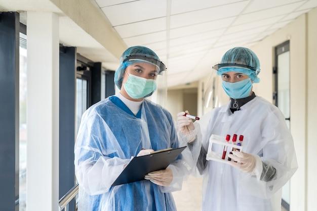 Deux femmes médecins avec des vêtements de protection tiennent un tube à essai avec un échantillon de sang du coronavirus dans une clinique moderne pandémie covid-19