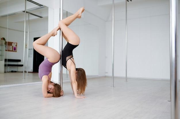 Deux femmes minces en formation de pole dance. danseuses professionnelles exerçant dans une salle de sport, pole dance