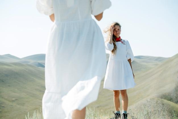 Deux femmes en mini-robes blanches simples et minces debout sur un pic au milieu de belles collines. se tenir l'un devant l'autre, se regarder. de derrière l'un d'eux. partie médiane du corps.