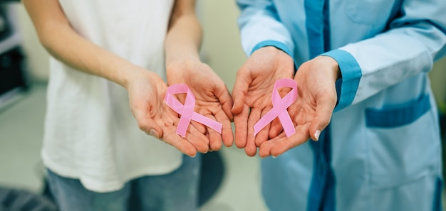 Deux femmes montrant un ruban de bâton médical de sensibilisation au cancer pour les soins de santé du sein féminin et la prévention du cancer