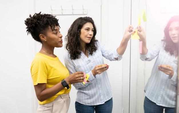 Deux femmes multiraciales au travail avec tablette