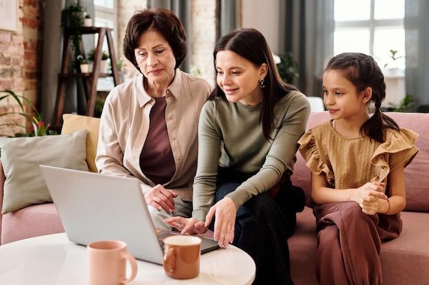 Deux femmes et une petite fille assise sur un canapé devant un ordinateur portable pendant un appel vidéo
