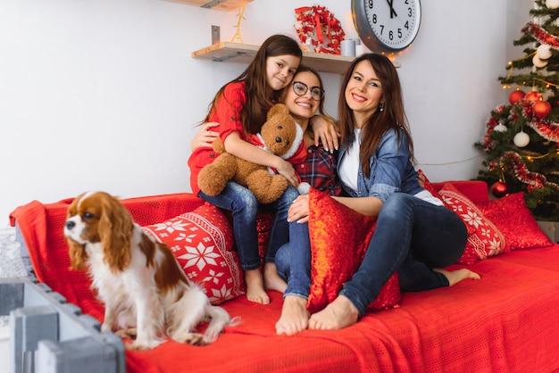 Deux femmes et une petite fille avec un chien s'amusent sur le canapé près de l'arbre de noël à la maison