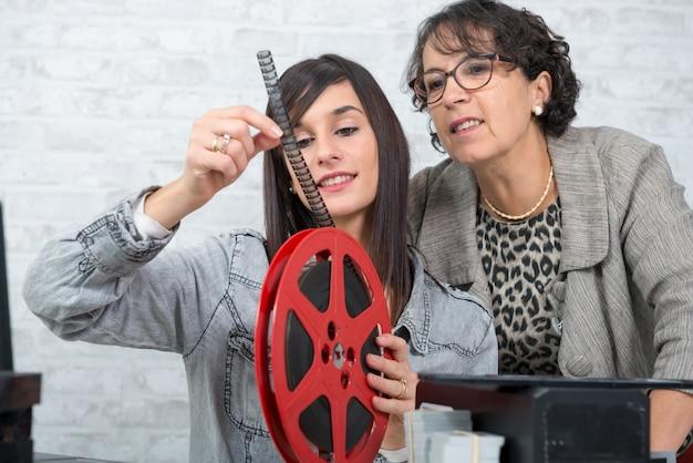 Deux femmes photographes regardant un film 16 mm