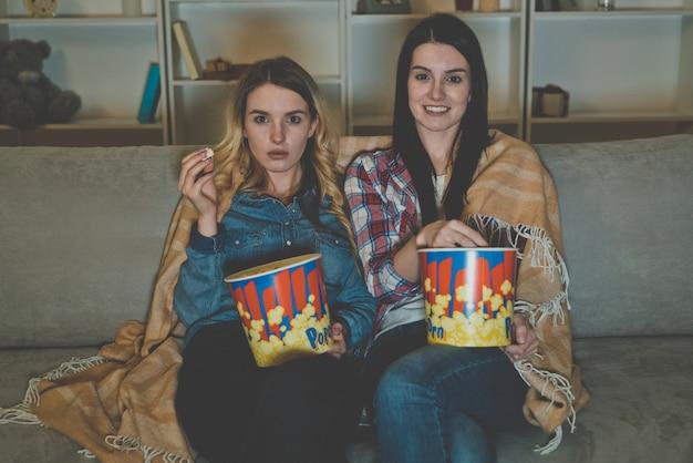 Les deux femmes avec un pop-corn regardent un film sur le canapé