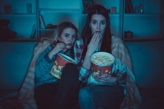 Les deux femmes avec un pop-corn regardent un film d'horreur sur le canapé