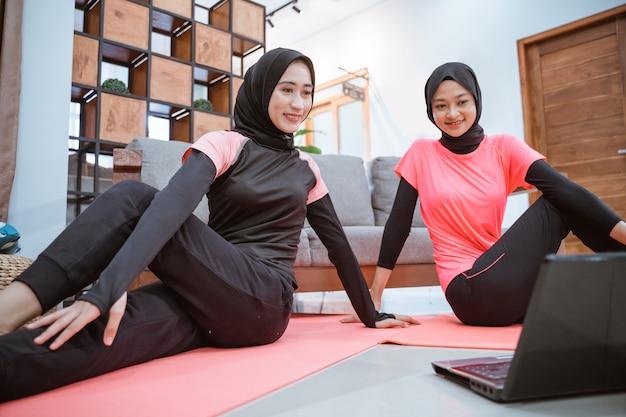 Deux femmes portant des vêtements de sport hijab sont assis sur le sol tout en réchauffant leurs hanches ensemble dans la maison