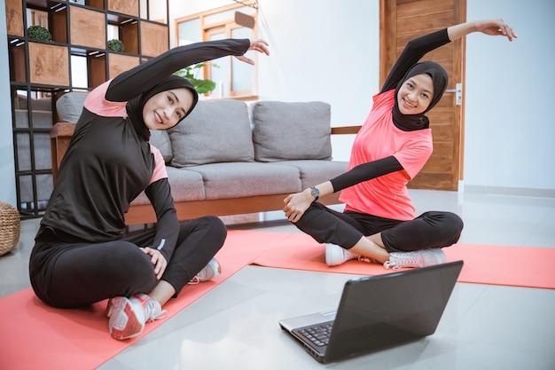 Deux femmes portant des vêtements de sport hijab sont assises les jambes croisées sur le sol, le corps penché sur le côté et les mains levées tout en réchauffant leurs bras ensemble dans la maison