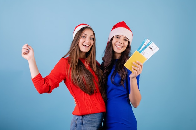 Deux, femmes, porter, chapeaux santa, à, billets avion, et, passeport, isolé, sur, bleu