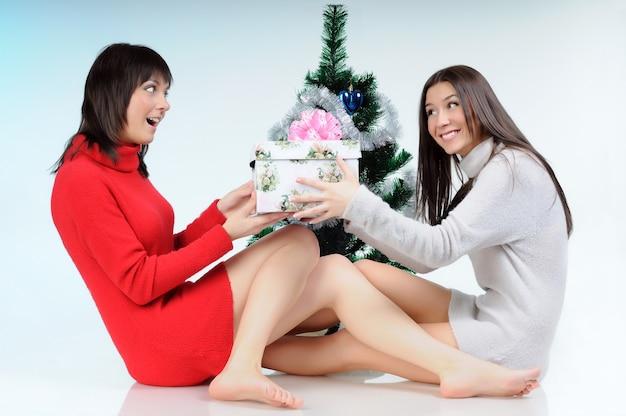 Deux femmes posant près de l'arbre du nouvel an
