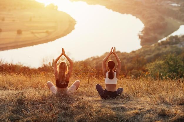 Deux femmes pratiquent le yoga et la méditation sur la montagne. ils méditent en haute montagne
