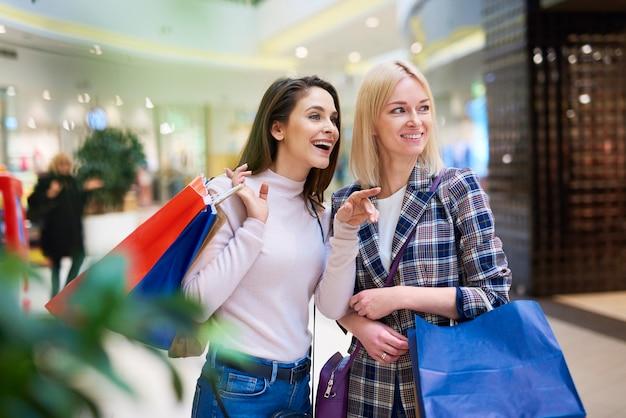 Deux femmes à la recherche d'une nouvelle boutique dans un centre commercial