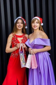 Deux femmes en robes de soirée élégantes à la recherche d'un sac cadeau. célébration de la fête du nouvel an