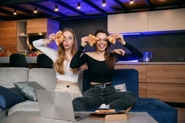 Deux femmes s'amusant à la maison, ouverture de la boîte à pizza, livraison de nourriture, fête à domicile
