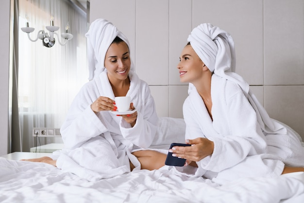 Deux femmes s'assoient au lit d'un appart'hôtel de luxe le matin avec une tasse, portent des peignoirs et des serviettes, regardent un smartphone, des réseaux en ligne, font du shopping, discutent, amitié et loisirs entre femmes