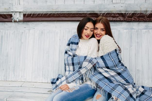 Deux femmes s'assoient sur un banc dans le parc et posent