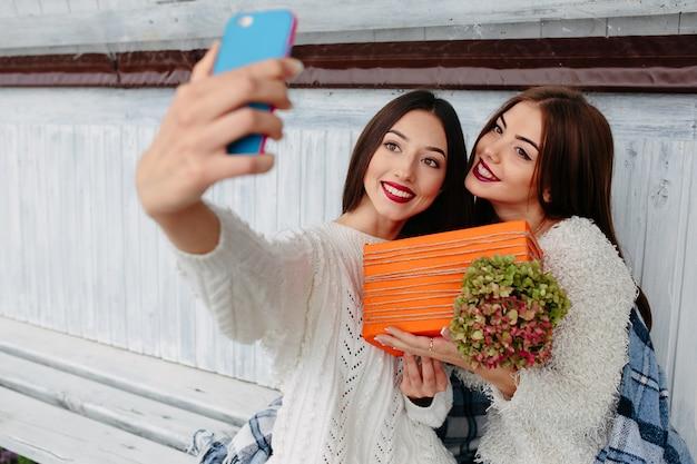 Deux femmes s'assoient sur un banc à l'extérieur et font un selfie avec un cadeau