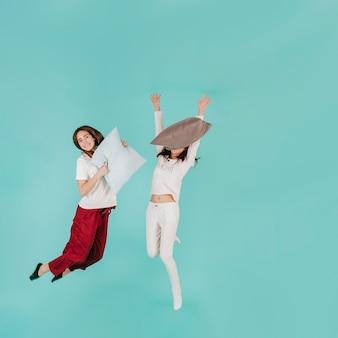 Deux femmes sautant avec des oreillers