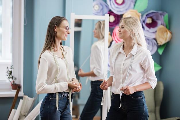 Deux femmes se tiennent devant le miroir avec des rubans adhésifs sur le cou atelier de tailleurs de mode
