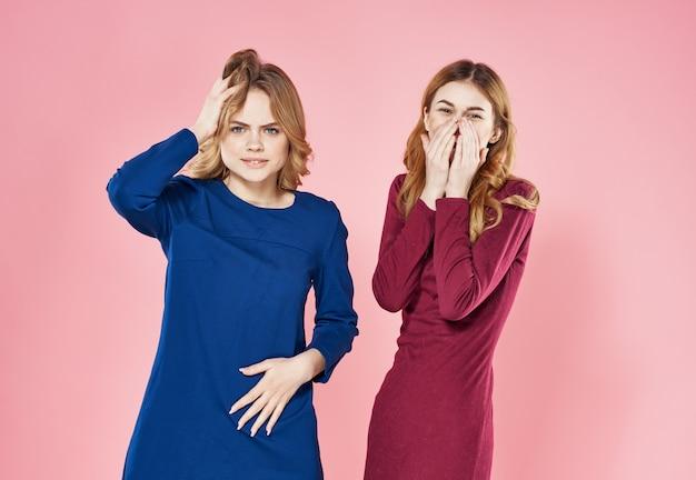 Deux femmes socialisant le studio de mode de vie de copines rose.