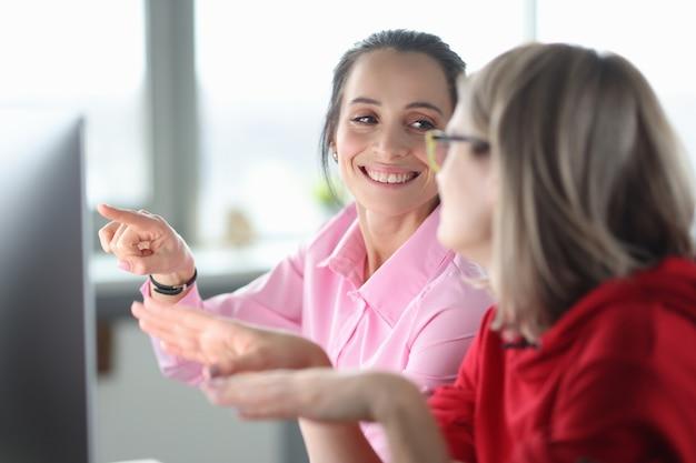 Deux femmes souriantes au bureau indiquent le moniteur. cours de programmation à partir de zéro concept